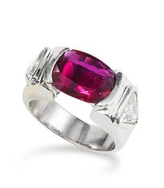 A ruby and diamond ring  The oval mixed-cut ruby, weighing 2.50 carats, to triangular-cut diamond shoulders, mounted in 18k white gold, the diamonds estimated to weigh approximately 0.60 carats in total, ring size 7¾