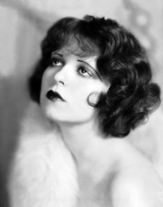 """Clara Bow, the original """"It Girl"""" was a famous 1920s silent film era star.  She was known for her red curls. Check out the bangs."""