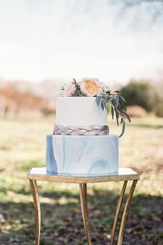 blue and grey marble cake with silver belt detail and fresh floral topper