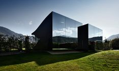 Peter Pichler designed a pair of connected holiday homes in Italy partially covered in glass and partially covered in mirrored glass reflecting the view.