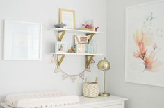 Love these styled shelves over the changing table in a coral and gold nursery!