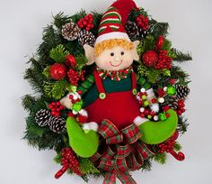 Cuando vi esta muñeca little elf sólo sabía que tenía que ir en una corona! Es tan dulce. Se centra en la corona con un lazo de tela escocesa de Navidad debajo de él. Conos de pino y selecciones con adornos de bastones de caramelo brillaba y bayas rodean el elfo adorable. A cada lado