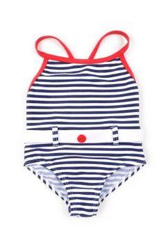 Traje de baño para bebe niña con diseño de rayitas en azul oscuro y blanco. Las tiras y el borde superior, en color rojo.