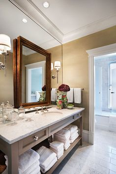 Double mirrors and a deep crown moulding add both sleekness & warmth to a more traditional bath. Design by Tom Stringer - Traditional Home®