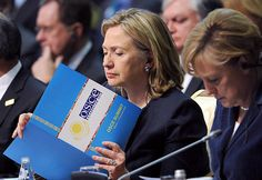 Astana, Kazachstan, Dec. 1, 2010 - U.S. Secretary of State Hillary Rodham Clinton, center, reads a document as she sits next to German Chancellor Angela Merkel at the start of the OSCE Summit at the Palace of Independence. (AP Photo/Geert Vanden Wijngaert)