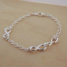 A thin but sturdy three infinity link bracelet with a lobster clasp closure Dimensions: 7 1/2 inch LWeight: 6.8 gramsSterling Silver stamped 925Handcrafted in I