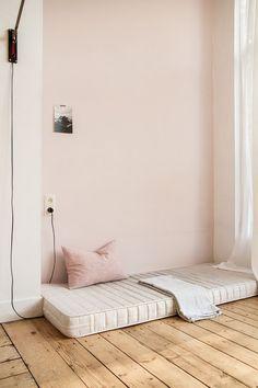 Palest pink in the bedroom against pale wood flooring .: