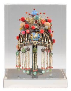 China - Headdress - Chinese, early 20th century, heavily jeweled and mounted with natural pearls, carved turquoise and seed pearls, centre set with jade brooch medallion with applied cloth puffs and red circular beads, 15-1/2 x 9 x 7 in.