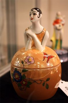 Noritake Art Deco auction at A.H. Wilkens  Noritake figural dresser jar  Pierrette in a caramel lustre dress with flowers and butterfly.