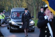 Procession: The funeral cortege carrying Mr Cox's coffin on the way to the ceremony in the...