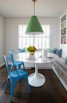 Green and blue breakfast nook features an emerald green light cone pendant light illuminating a Saarinen Dining Table lined blue Tolix Chairs and a built-in L shaped banquette situated under built-in bookcases.