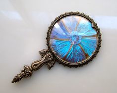 Morpho hand mirror. €25,00 ($31.00), via Etsy. This lovely hand mirror is decorated with morpho wings in a flower pattern, behind glass. http://www.etsy.com/listing/94549565/morpho-hand-mirror?ref=sr_gallery_4&ga_search_query=morpho+&ga_order=most_relevant&ga_view_type=gallery&ga_ship_to=ZZ&ga_min=0&ga_max=0&ga_search_type=all