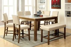 Counter Height Table with Stone Inserts. Upholstered chairs with nailhead trim.