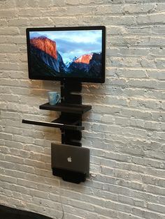 The StandCrafted minimalist, modular, wall-mounted standing desk in black high density industrial grade plastic