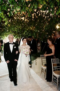 An amazing picture of the bride and her father walking down the tree-lined aisle | Brides.com