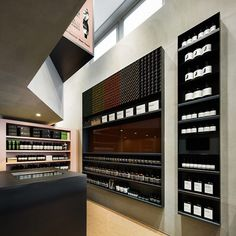 Aesop Shibuya store by Torafu Architects, Tokyo : In order to limit the variety of the materials used, the shelves and counter are finished in blackened steel, which is also the basis for storage doors assimilated into the mortar wall or mirror wall; the basin that is Aesop's feature is set near the entrance to effect a good view from the passage.