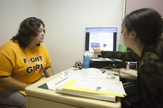 """Amy Ball, right, counsels Wanda Perry, 48, left, about possible options for health insurance in Delaware once the new exchanges open on Tuesday. Christiana Care Health System in Wilmington, Del., is providing marketplace """"guides"""" to help consumers navigate the system. Perry is currently unemployed and her husband is self-employed. Neither has health insurance now."""