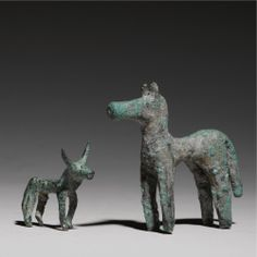 TWO GREEK BRONZES, GEOMETRIC/ARCHAIC, 8TH/7TH CENTURY B.C. comprising a horse standing with ears erect, crested mane, and cylindrical muzzle, and a bull with grooved mouth and indented circular eyes.