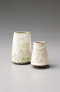 Lucie Rie - Tapering vases, Stoneware, flowing white lime glaze with brown manganese speckles coming through from the body material beneath. Taller: 5 3/8 in. (13.7 cm.) high, 1967
