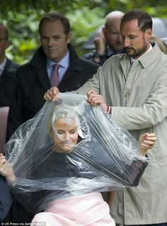 CP Haakon of Norway helps his wife CP Mette-Marit of Norway put on her rain poncho during Silver Jubilee celebrations. June 29 2016
