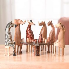 A work of wit and artistry. Each animal - rhino, cheetah, lion, giraffe, elephant, zebra -- is handcarved from a single piece of mahogany and hand-painted. The table is shaped like Africa; the set includes six little glasses and a wine bottle. Animals about 8' high. Sales of this Fair Trade product benefit young women in Kenya.