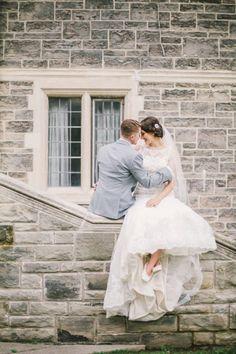 Bride and groom sitting on church wall #weddingportrait