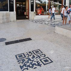 """""""QR Code"""" mosaic in the pavement in Chiado Square, Lisbon, Portugal - photo by LisbonLux;  """"By the terrace of the Benard cafe, is a 1-square-meter QR code made of cobblestone, to provide tourist information about the neighborhood on your smartphone."""""""