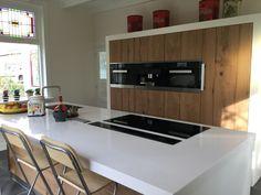 Landelijke houten keuken met wit aanrechtblad en inbouw afzuigkap