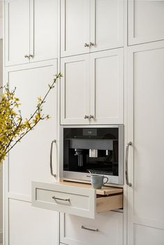 Floor-to-ceiling white shaker cabinets adorned with polished nickel pulls are positioned framing a coffee machine placed on a pull out shelf.