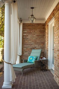 Brick walls, brick floors, a white paneled ceiling and traditional white columns lend Southern charm to this covered porch. A cushioned lounge chair provides comfortable seating and a splash of color, and a lantern pendant completes the space.