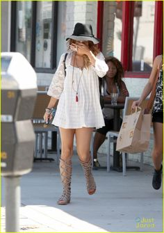 Vanessa Hudgens in a cute ivory boho tunic dress and flat gladiator sandals that look almost like boots.
