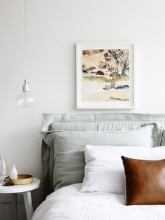white bed styled with gray and brown leather pillows