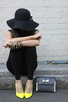 Floppy wide-brim hat and neon heels.