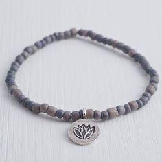 Breathe in the Ocean von A Pinch of Salt - Elastisches, handgemachtes Armband aus Kokosnussschale mit einem Lotusblüten-Anhänger aus Sterling Silber.