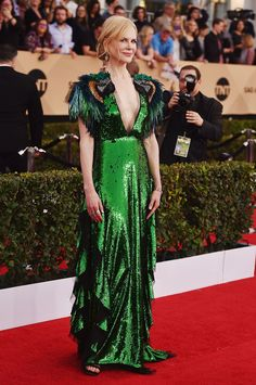Sparkling green Gucci gown, decked out with embellished and feathered parrot designs on each of her sleeves