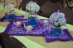 A picnic themed rehearsal dinner at a lake house..  Blue and purple were the wedding colors.  Purple bandanas, blue hydrangeas in mason jars (cut a hole in the lid to hold the flower upright), blue tinted water, blue candles in jars, topped with purple checked ribbons and bows!