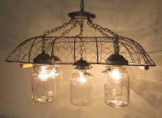 We need to make more of these chicken wire chandeliers with mason jars. The Lamp Goods Dining Table Lighting, Rustic Lighting, Vintage Lighting, Kitchen Lighting, Home Lighting, Cabin Lighting, Mason Jar Chandelier, Mason Jar Lighting, Mason Jar Lamp