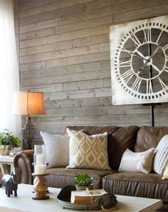 Love this Farmhouse living room with a brown sofa, rustic gray wood walls, warm white tables and great accessories!