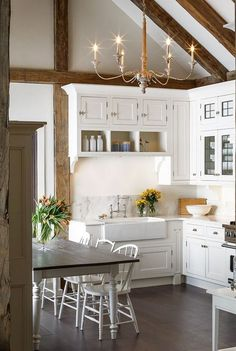 White modern farmhouse kitchen decor ideas: A breathtaking white kitchen with traditional decor and farmhouse style. Rustic wood beams, farm sink, and shaker style cabinets.