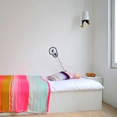 12 White Rooms with Pops of Color: This is a bedroom in a concept guest house in Ghent, Belgium, above the gallery Sofie Lachaert, designed by Droog Design. It allows customers to experience Droog's products in a fully equipped apartment. It's called Droog for Rent. The colors of the Color Plaid Blankets by Thomas Eyck are simultaneously soft and bright.