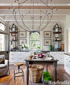 The scale of the chandelier by Tim Adams, from Savannah's Paris Market, and of the antique étagères, from Charleston's South of Market, creates drama in Mary Jo Bochner's Savannah, Georgia, kitchen.