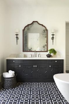 Black and white Moroccan mosaic floor tiles lead to a stunning black washstand complemented with black star cabinet doors contrasted with white knobs and an ivory quartz countertop paired with an ivory quartz backsplash fixed behind a satin nickel gooseneck faucet.