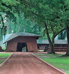 """Frank Lloyd Wright couldn't design an ordinary-looking building,"" says producer Joel Silver, who restored the little-known Auldbrass, Wright's 1939 plantation in Yemassee, South Carolina. A crushed-brick walkway leads to the barn. ""By folding the roof down and the corners of the doors back, Wright created something origami-like,"" Silver notes. December 1993"
