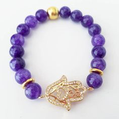 Hamsa hand stretch bracelet with purple jade beads. This bracelet can be made in any color - please contact me for custom orders! The hamsa hand is gold and covered in crystals so it really sparkles! ♥ Please treat your jewelry gently, as some materials can be extremely fragile.