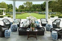 The loggia at this Southampton, New York, Colonial Revival home designed by Mario Buatta includes Bielecky Brothers wicker furniture and ceramic garden seats from John Rosselli Antiques. | archdigest.com