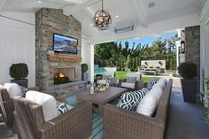 Amazing covered patio with covered ceiling accented with a bronze sphere pendant illuminating a u shaped furniture arrangement composed of a wicker sofa and wicker chairs accented with navy trellis pillows facing a teak coffee table atop a green and blue striped outdoor rug facing a stone fireplace with flatscreen TV.