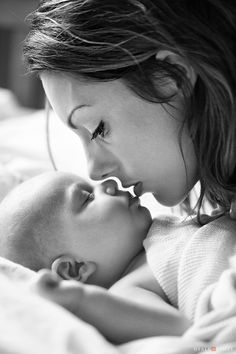 Black and white picture of mother kissing baby