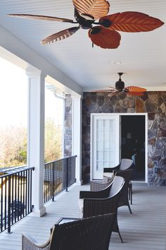 Love this second floor balcony! It features white columns and tropical style outdoor ceiling fans with lots of places to sit and enjoy the view ©Balducci Builders, Inc.