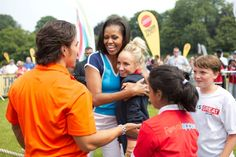 """First Lady Michelle Obama hugs former Olympic gymnast Nastia Liukin during a """"Let's Move! London"""" event at Winfield House in London, England, July 27, 2012. Olympic short track speedskater Apolo Anton Ohno, orange looks on. (Official White House Photo by Sonya N. Hebert)"""