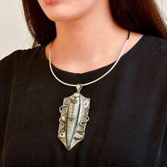 Pandantiv lucrat manual din argint, frumos ornamentat cu  fosile pietrificate de melci marini.  Cod produs: DP276 Greutate: 64.09 gr. Lungime: 11.00 cm Lățime: 4.50 cm